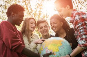 Multiracial teens holding a globe