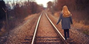 young woman walking along railroad tracks